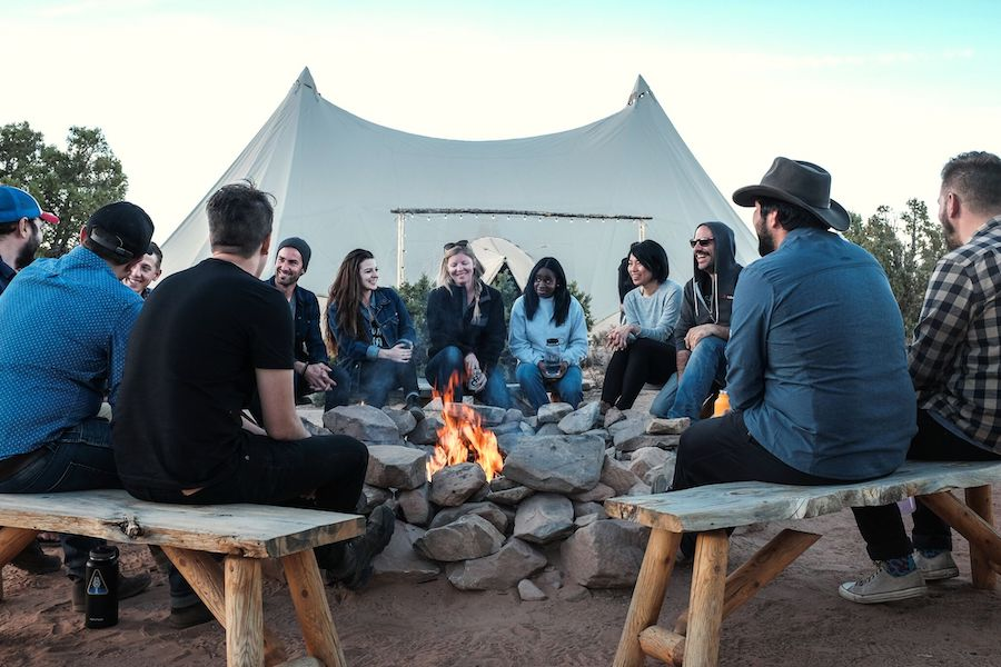 Group of people surrounding a campfire. I am in the middle of the photo laughing in friends.