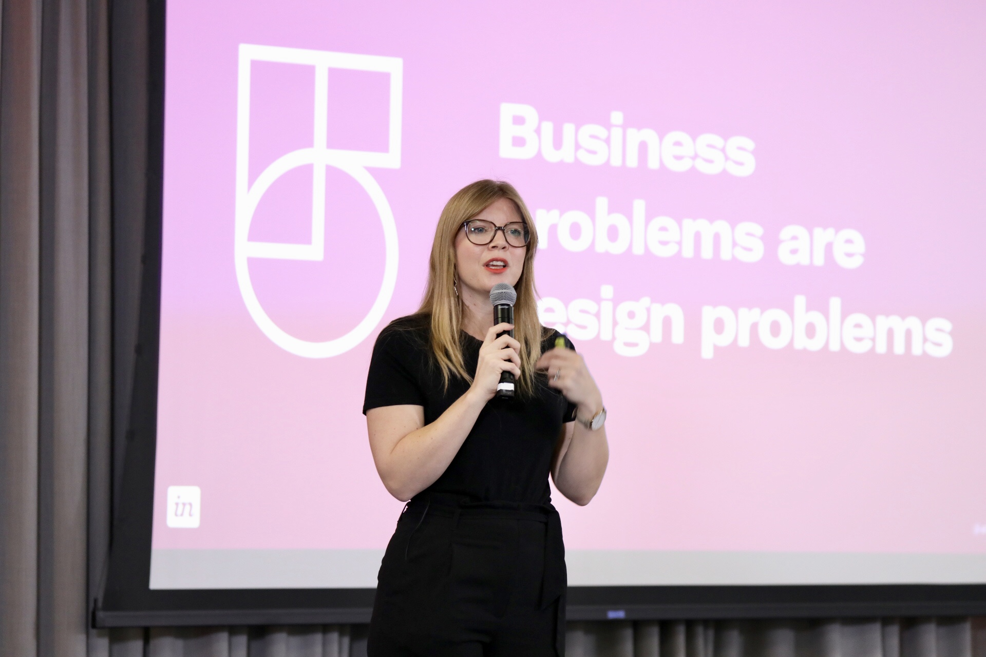 Me in front of a slide reading 'Business problems are design problems'